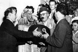 1948-Ettore-Gian-Ferrari-e-Dino-Villani-consegnano-la-forma-di-formaggio-a-Giuseppe-Gorni-300x200
